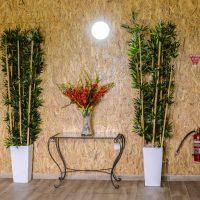קונסולת זכוכית עם זר פרחים, שני עציצים וארונית בבית הספא
