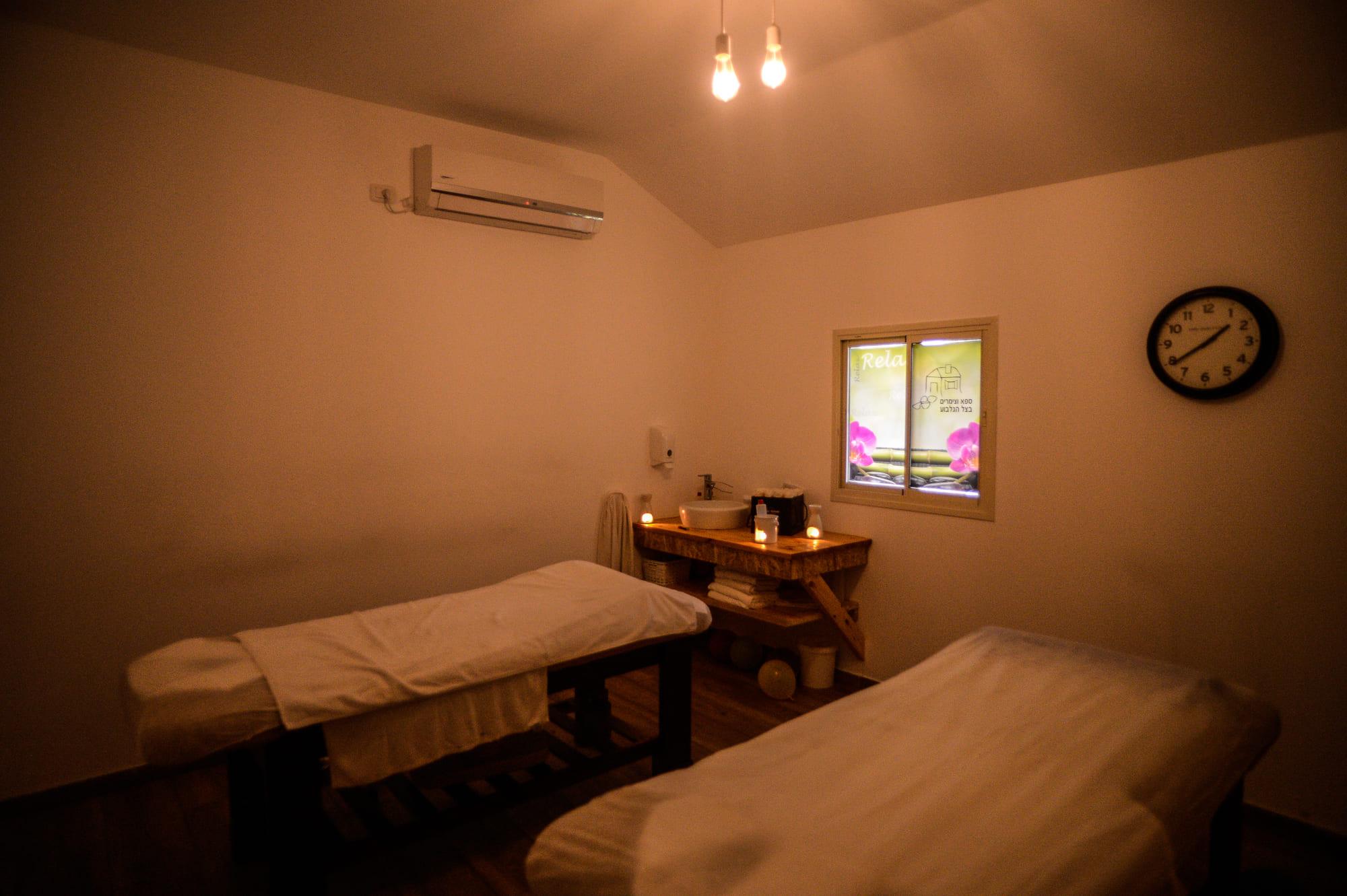 חדר הטיפולים בספא בצל הגלבוע מכיל: 2 מיטות, נרות דולקים, כיור לשטיפת ידיים, מגבות.