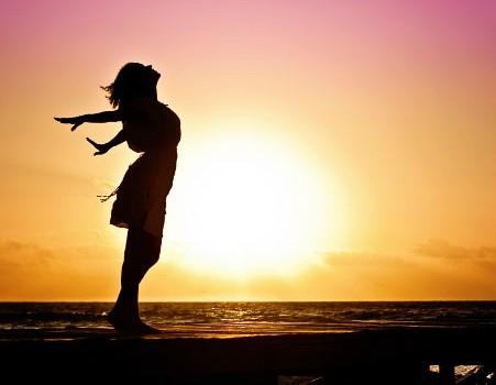 צלמית של אישה על רקע שמש שוקעת וים